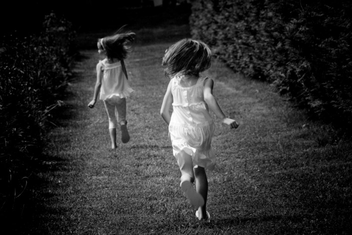 Sisters running through a garden in the summertime.